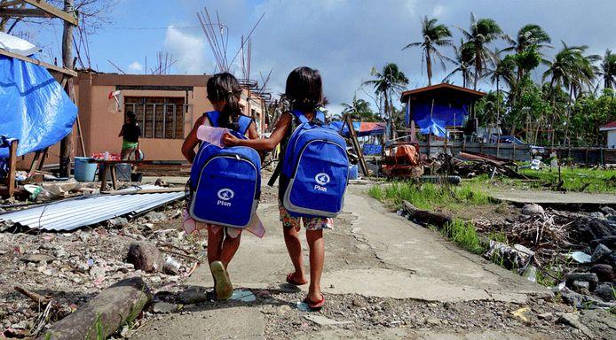 Filipijnse kinderen met een rugzak van Plan Internationaal na de orkaan Haiyan in 2013.