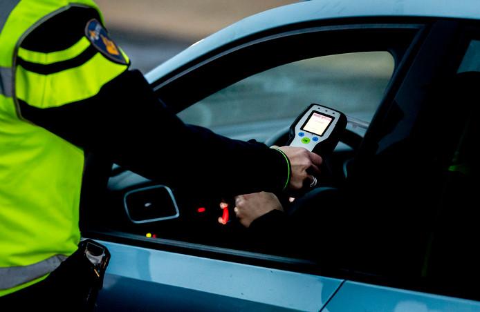 Archiefbeeld: Een politieagent voert een alcoholcontrole uit tijdens een verkeerscontrole
