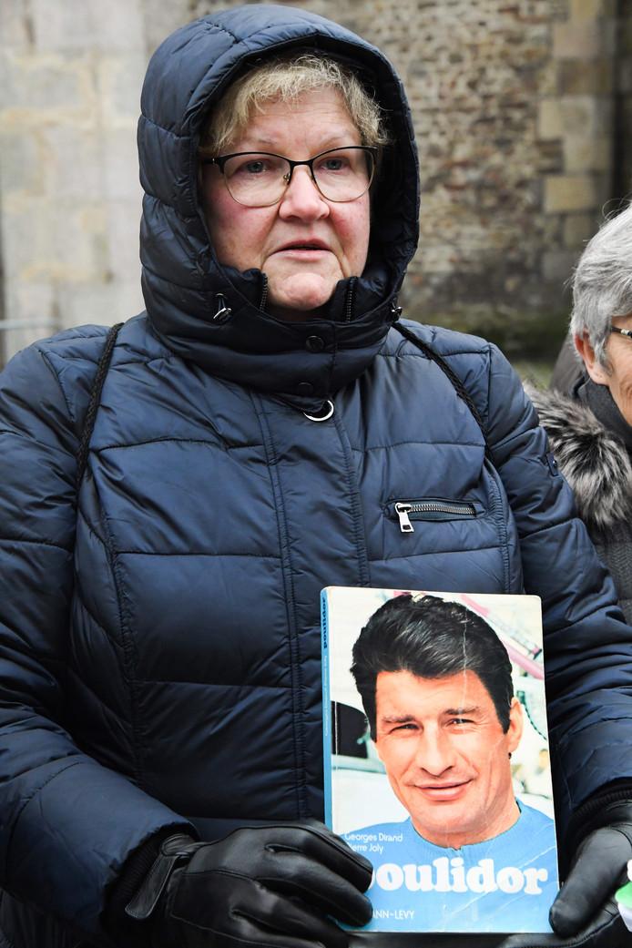 Een vrouw met een boek over Raymond Poulidor.