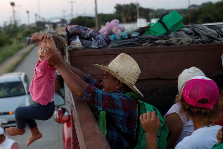Een van de migranten die deelneemt aan de 'karavaan' richting de VS, helpt een kind aan boord. 8 november, Santo Domingo Ingenio, Mexico. Beeld Reuters