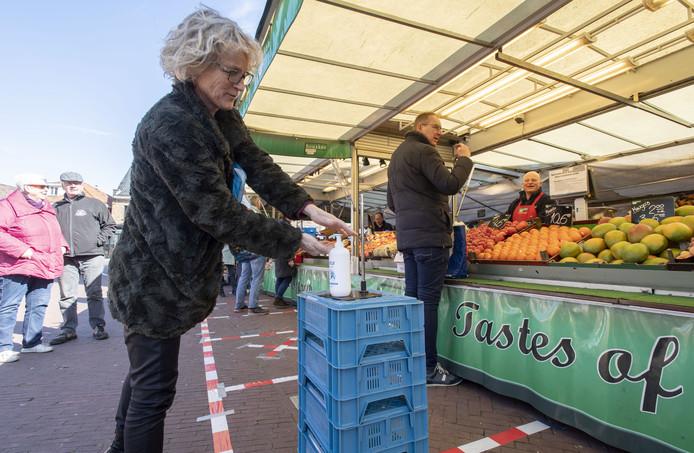 Pompjes met desinfecterende crème en afzetlint om de vereiste afstand te bewaken: veiligheid staat voorop bij de kooplieden op de Haaksbergse warenmarkt.