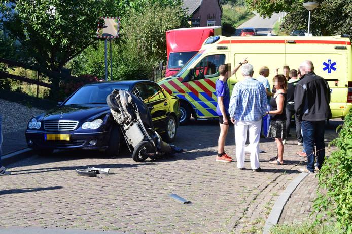 De scooter ligt tegen de auto aan.