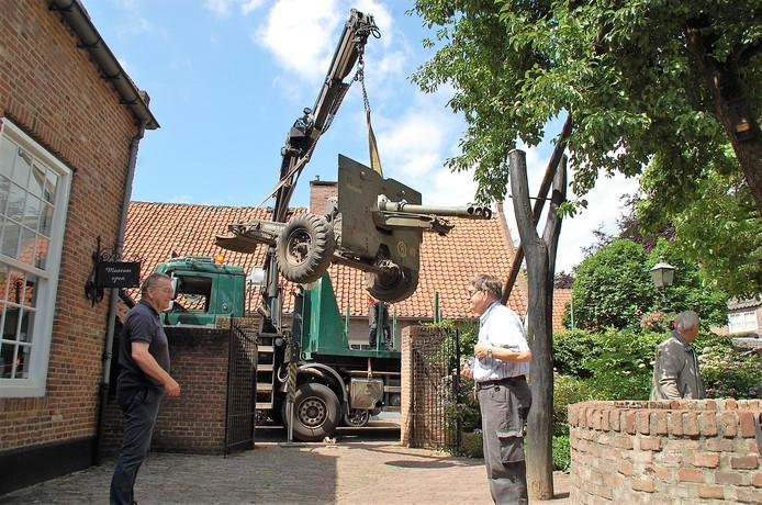 De houwitser wordt voorzichtig op het terrein van De Vier Quartieren gehesen. Han Smits van het Kapittel Oirschot en Jan van Vroenhoven van heemkundekring Den Beerschen Aard kijken toe.