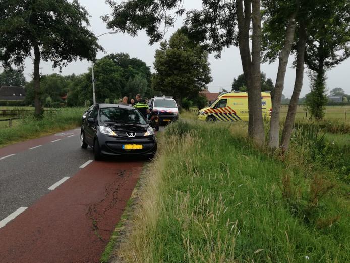 Hulpdiensten ontfermen zich over de bestuurder van de scooter.