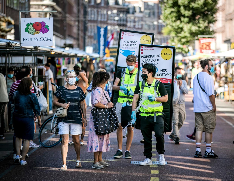 In de Albert Cuypstraat worden gratis mondkapjes uitgedeeld. Beeld Hollandse Hoogte /  ANP