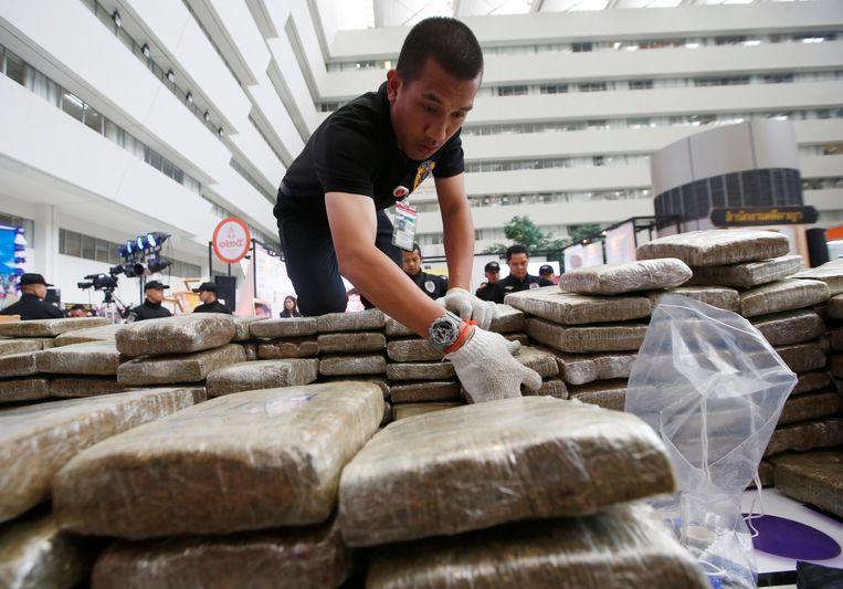 Een Thaise politieman met in beslag genomen marihuana in de hoofdstad Bangkok. Beeld AP