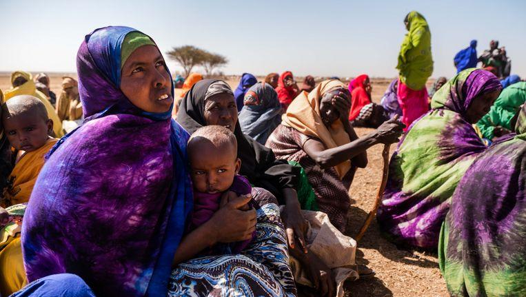Vrouwen en kinderen wachten al zitten geduldig op de komst van de vrachtwagen. Op de voorgrond: Mama Sodoh met dochtertje Kadan.