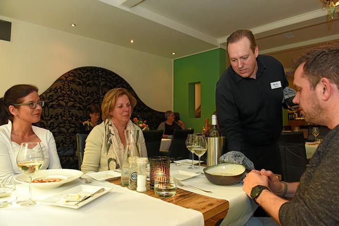 Gastheer Arthur Braat aan tafel bij zijn gasten.