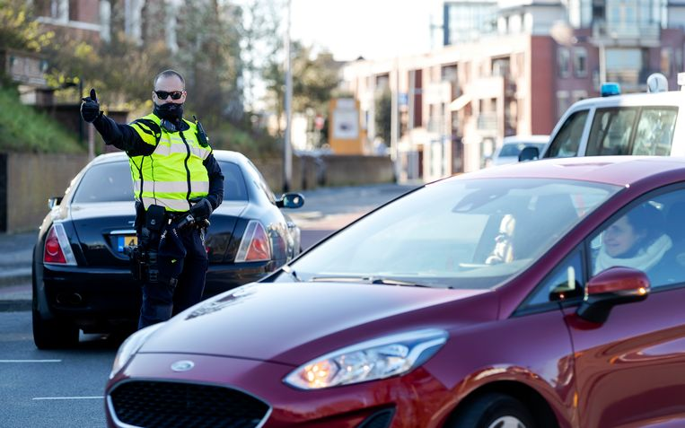Een politie-agent houdt in verband met de coronacrisis dagjesmensen tegen op de toegangswegen naar de boulevard en het strand van Noordwijk.  Beeld ANP