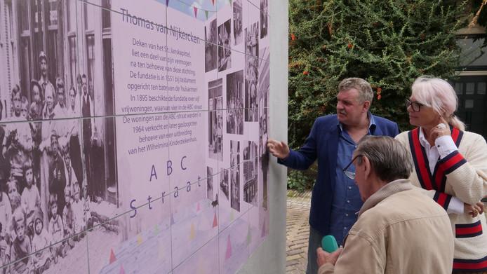 Leo Saurens (links), Arnoldes Saurens (midden) en Jackie Sleper (kunstenaar) bekijken de foto's op het kunstwerk.