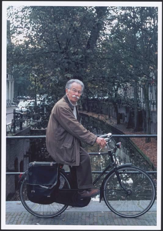 Dick Bruna op de fiets op een brug over de Nieuwegracht.