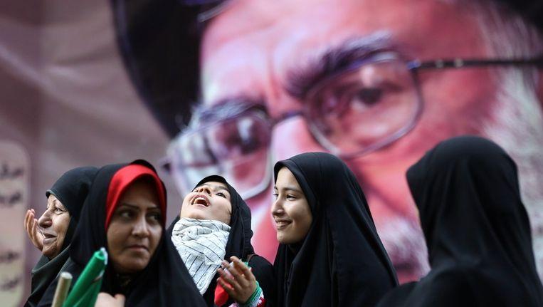 Vrouwen lopen langs een portret van ayatollah Khamenei. Beeld AFP