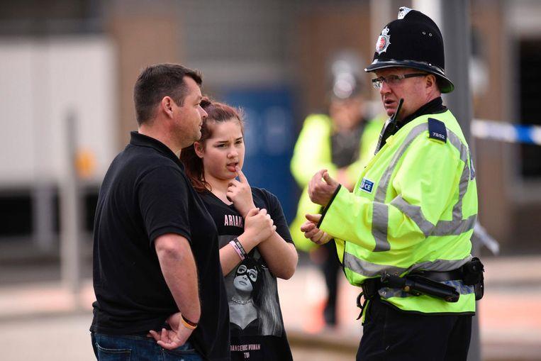 Een meisje en haar vader praten met een agent in Manchester. Beeld afp