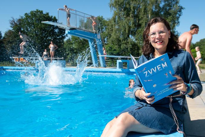 Irma Kokx met haar boek op de rand van het Bredase openluchtzwembad Wolfslaar.