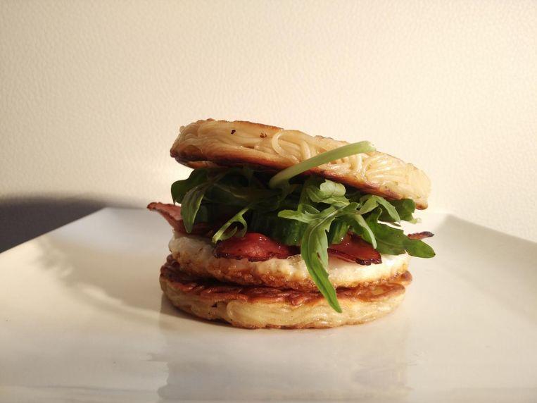De 'Breakfast Burger', een nieuwe noodleburger die Xin en Gilles lanceren op Tomorrowland. De ingrediënten: twee noodleschijven, een crunchy spiegeleitje, bacon, komkommer, rucola en een zelfgemaakt sausje.