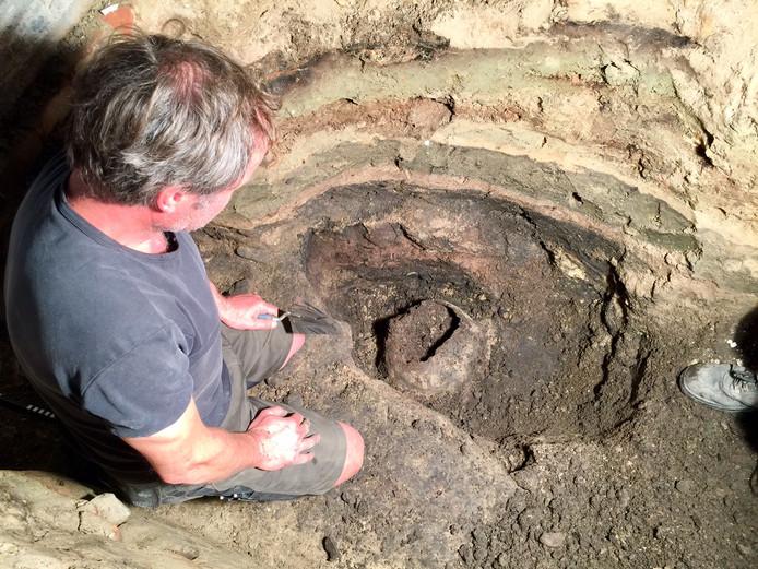 Archeoloog Hans Oude Rengerink bij opgegraven kogelpot in voormalig hotel De la Poste in Ootmarsum.