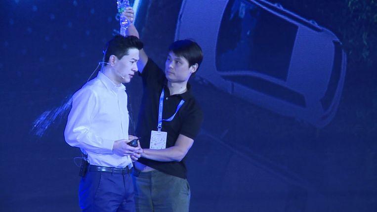 Tien minuten nadat Baidu-topman Robin Li aan zijn toespraak was begonnen, beklom een man het podium en goot zijn flesje water leeg over het hoofd van de miljardair.