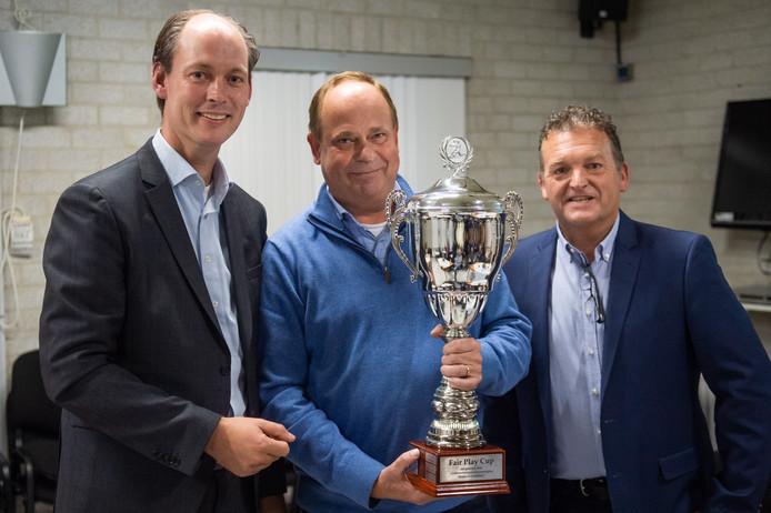 VV Bavel-voorzitter Eric Joossen toont de beker. Hij wordt geflankeerd door wethouder Daan Quaars (links) en Rob Luyken van de COVS.