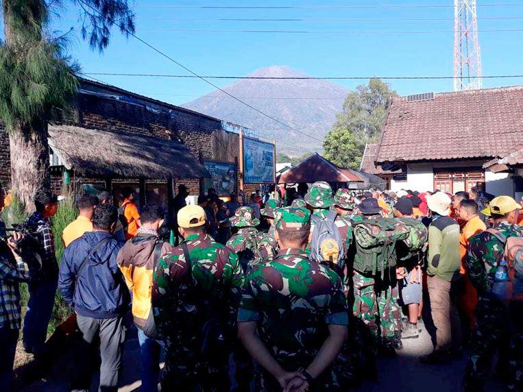 Indonesische soldaten en reddingswerkers maken zich klaar om toeristen te evacueren van de Mount Rinjani, de berg op de achtergrond, in East Lombok in Indonesië.