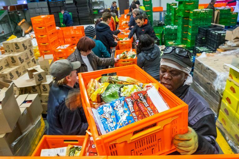 Vrijwilligers, werkelozen en verstandelijk gehandicapten aan het werk bij de voedselbank in hun distributiecentrum in Rotterdam-West.  Beeld null