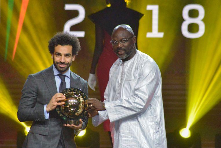George Weah, president van Liberia en ex-topvoetballer, overhandigt Salah zijn trofee.