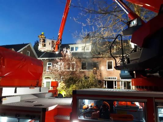 De brandweer aan het werk met de hoogwerker bij de woningbrand in Arnhem.