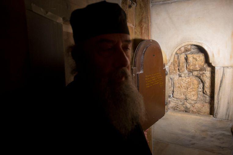 Een Griekse priester bij een raam dat uitgeeft op de binnenkant van de graftombe van Jezus. Het zou een deel van de originele stenen muur zijn van de tombe.