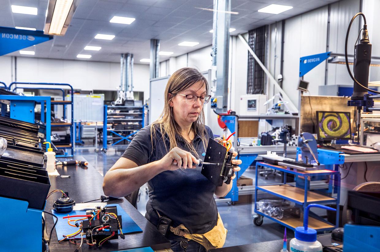 Een medewerker van Demcon schroeft de kernmodule voor het beademingsapparaat in elkaar.  Beeld Raymond Rutting / de Volkskrant