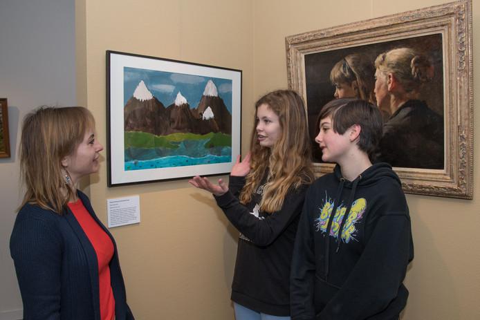 Leerlingen Hester Drent (rechts) en Charlotte Smit met links projectcoördinator Ewa Maziarz bij hun kunstwerk. Rechts het bekende 'Suusje aankleden'.