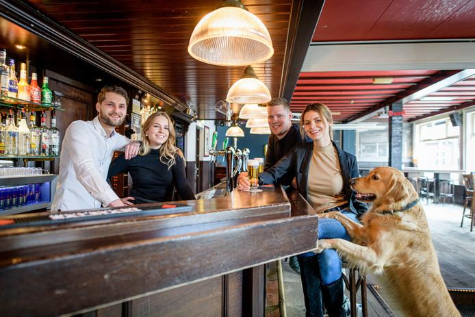 Dennis Bos en en zijn vriendin Naomi Nijboer (rechts) en hond Paco die vertrekken als eigenaar van De Musketier. Max Bosch en Marente Dijkstra (achter het schap) nemen het over.