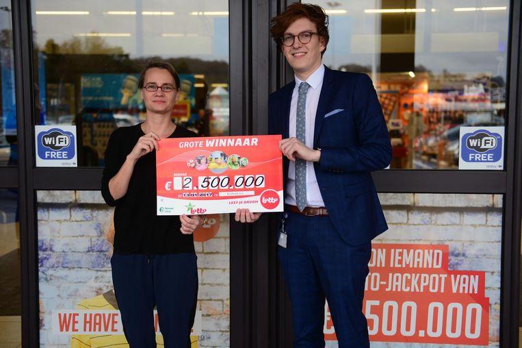 Kiki Vervloesem en Bram Vermesen tonen de cheque van de Lotto-winnaar in de Carrefour van Korbeek-Lo.