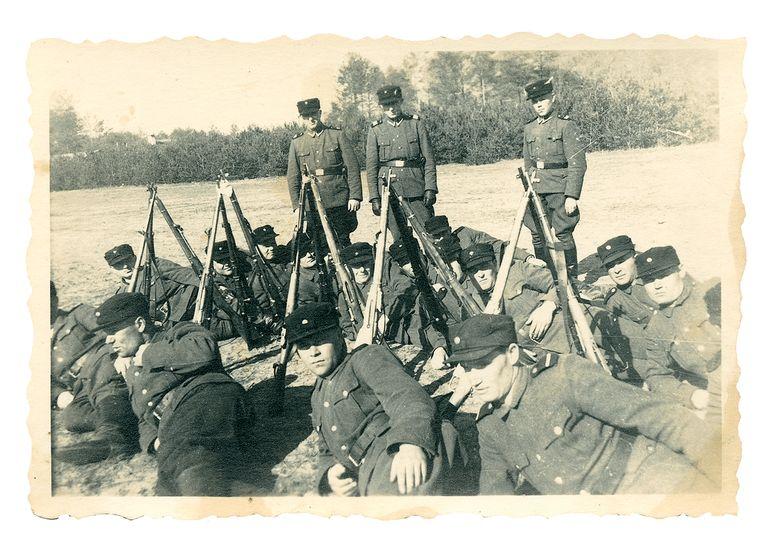 Op deze foto van kampbewakers is linksboven de kappersbarak te zien, waar Joodse vrouwen werden geknipt voordat ze werden vergast. Beeld United States Holocaust Museum