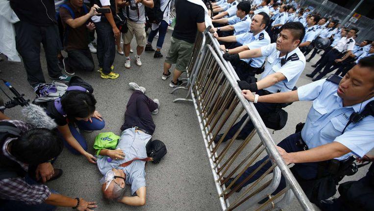 Politiemensen in Hongkong proberen een demonstrant van zijn plek te krijgen. De politie in Hongkong plaatste vandaag nieuwe dranghekken bij het kantoor van stadsbestuurder Leung Chun-ying. De pro-democratiebetogers eisen zijn terugtreden, zo niet dan dreigen zij het gebouw te bezetten. Beeld reuters