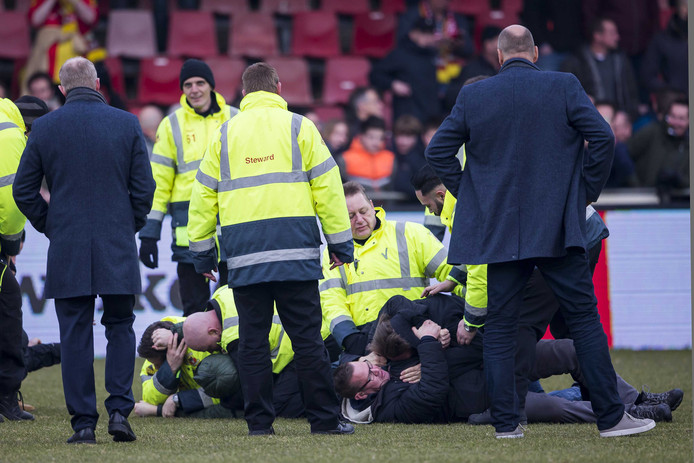 Supporters van Go Ahead Eagles worden overmeesterd op het veld.