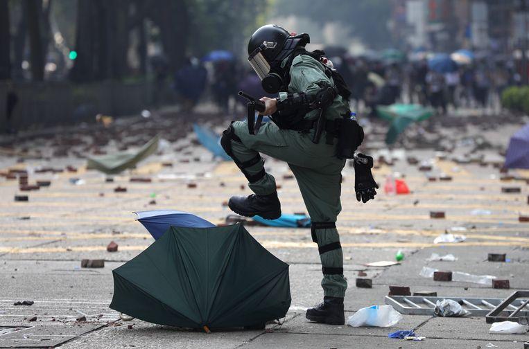 Een agent van de oproerpolitie stampt de paraplu van een demonstrant plat in Hongkong, waar Wang Liqiang volgens hemzelf actief zou zijn geweest als spion. Beeld EPA