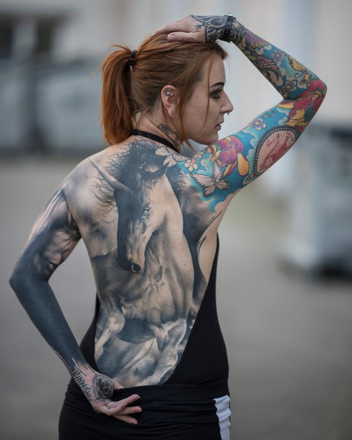 Een bezoeker van de internationale tattoo-conventie in het Duitse Frankfurt toont trots haar tattoo van een eenhoorn aan de fotograaf. Foto Boris Roessler