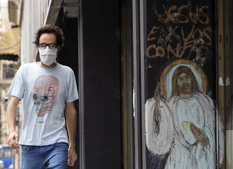Een man met een mondkapje loopt langs een graffiti-afbeelding van Jezus Christus in Buenos Aires.  Beeld AFP