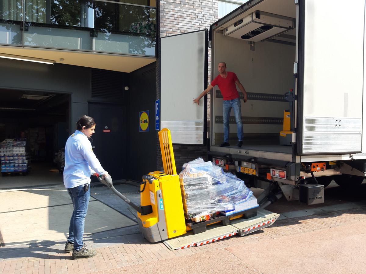 Medewerkers van de Lidl in Wijchen laden goederen uit de defecte koeling over in een koelwagen die in allerijl is opgeroepen.