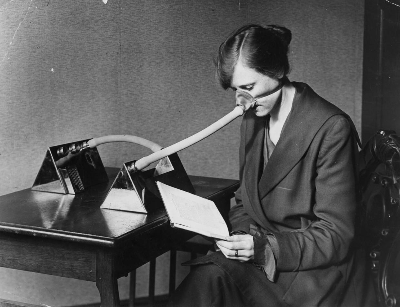 Een vrouw draagt een griepmasker in 1919. Wetenschappelijke kennis over virussen ontbrak destijds.  Beeld Getty Images