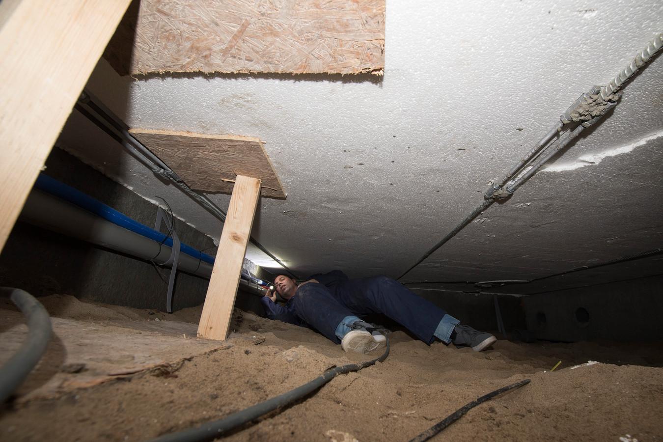 Bouwinspecteur Veerman bekijkt vanuit de kruipruimte hoe de vloer is 'gestut' met houten balkjes.