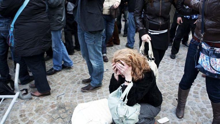 Een bezoeker van de Nationale Dodenherdenking zit gewond op de grond. Foto ANP Beeld
