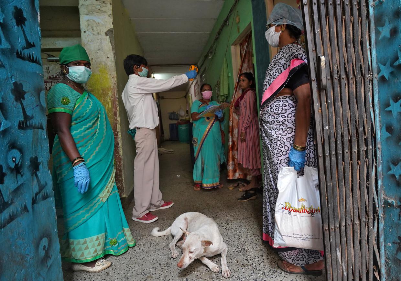 Gezondheidsmedewerkers met mondmaskers checken de temperatuur van een bewoner in Mumbai.   Beeld REUTERS