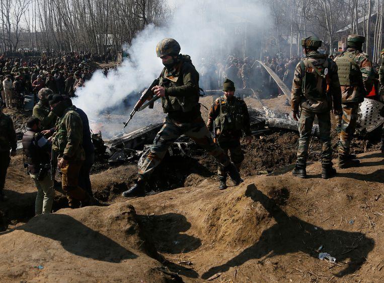 Indiase soldaten bij het wrak van een woensdag door Pakistan neergeschoten toestel in Kashmir. Beeld AP