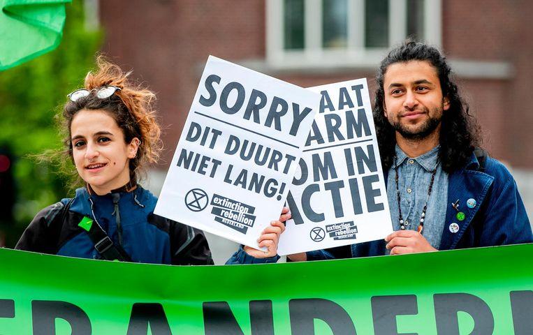 Klimaatactivisten van Extinction Rebellion blokkeren een weg bij het Roelof Hartplein in Amsterdam.  Beeld ANP