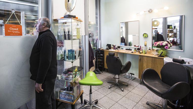 Jozeph Koleh in zijn kapperszaak van tien vierkante meter in Amsterdam-Noord Beeld Eva Plevier