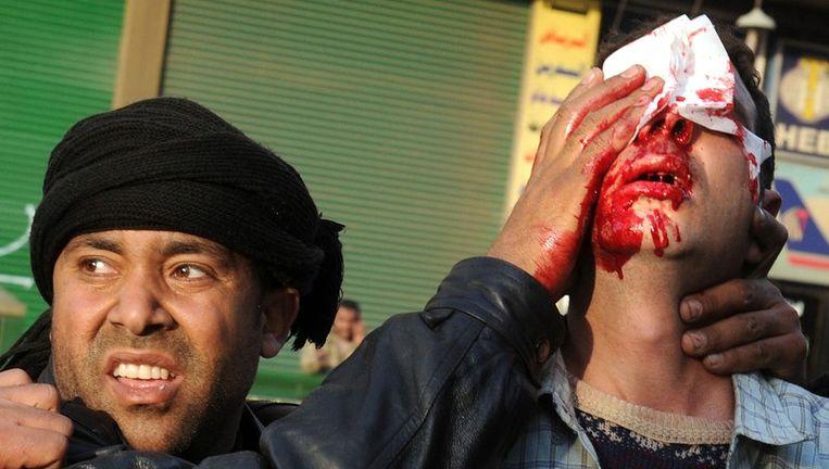 Een Egyptische man helpt een gewonde anti-Mubarakdemonstrant in Caïro. Beeld afp
