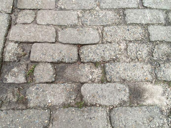 Heel wat rechthoekige betonstenen zijn in mindere staat.