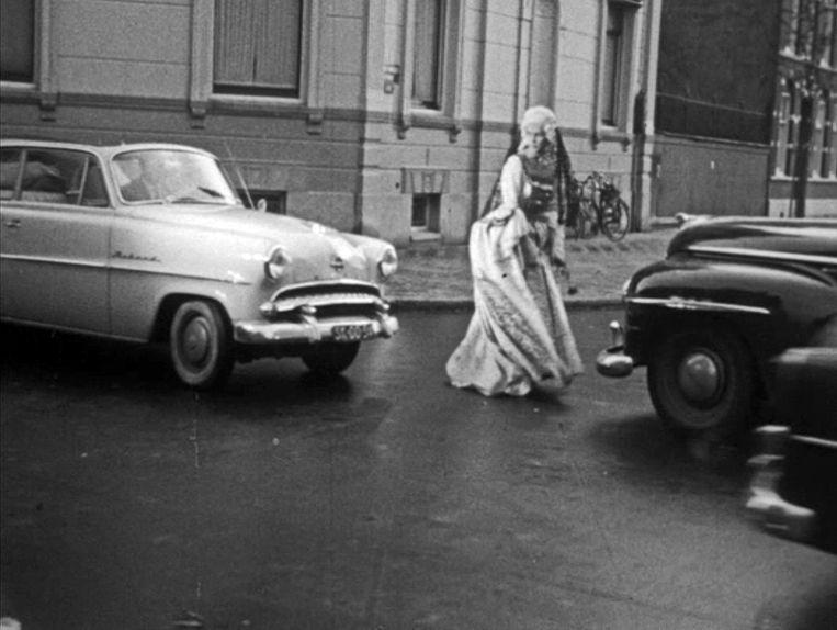 In de verkeersfilm uit 1957 belandt de 18de-eeuwse Carolientje tussen de auto's op de Van Eeghenstraat, daarna steekt ze modern gekleed de Apollolaan over. Beeld