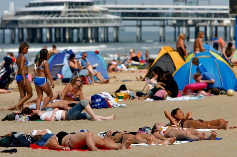 Strandgangers in Scheveningen, met achter de bekende Pier.