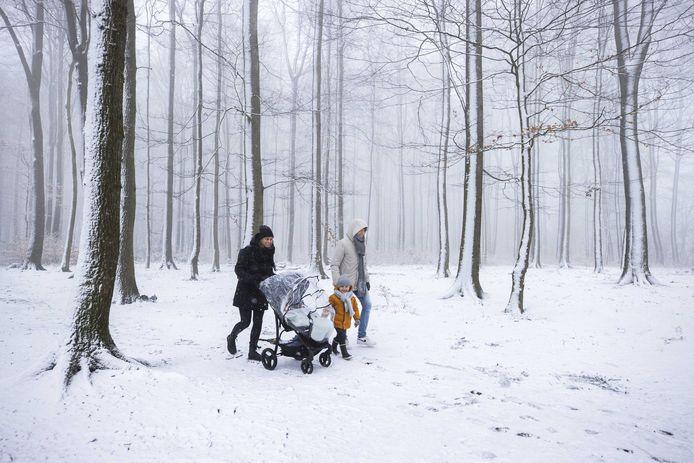 Een gezin wandelt door de sneeuw bij Het Drielandenpunt in Vaals.